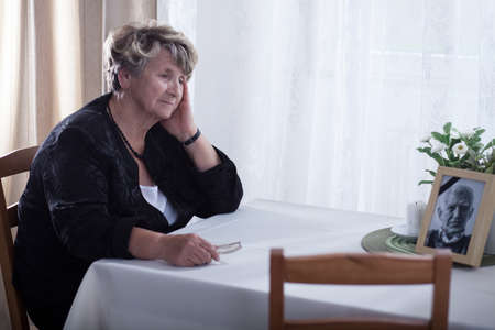 Senior woman looking at dead husband's picture