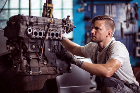 Photo of uniformed car technician maintaining automotive engine