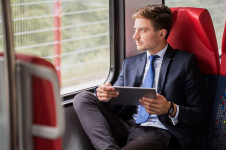 Image of male commuter in suit traveling by train