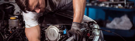 Close-up of motor mechanic repairing car engine