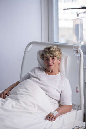 Elderly woman is lying in hospital and smiling