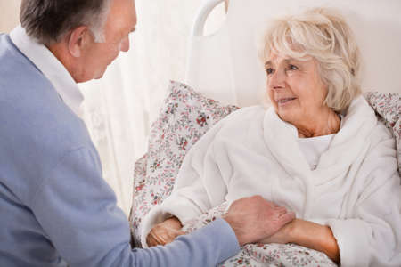 Old man is nursing his very ill wife