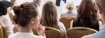 Young woman is listening at the conference
