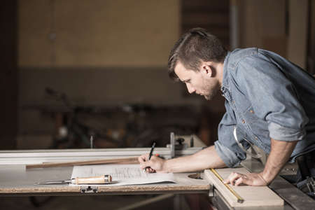 Photo for Carpenter at work carefully looking at the plans - Royalty Free Image