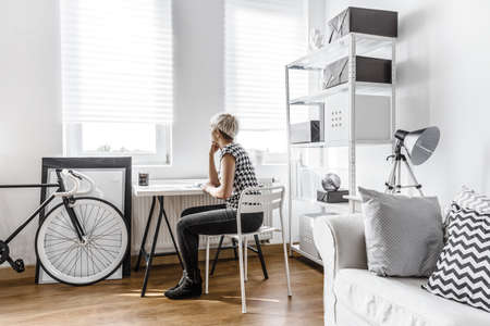 Thinking woman sitting at the desk in modern studio