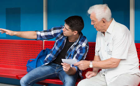 Horizontal view of young man helping retiree