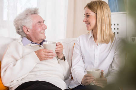 Photo of volunteer in care home talking with old man