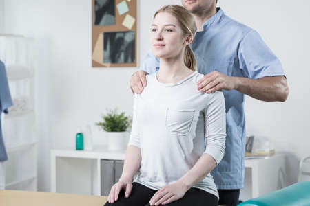 Image of physical therapist helping female patient with back pain