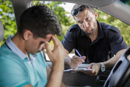 Man in a car and the policeman with traffic ticket
