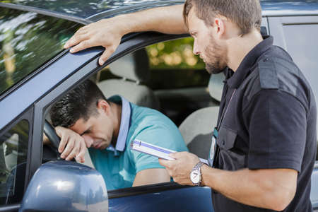 Sad young man in car fined by police officer