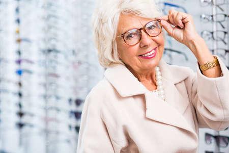 Elderly woman choosing reading glasses in optical shop