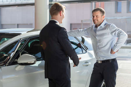 Image of smiling car showroom client talking with seller