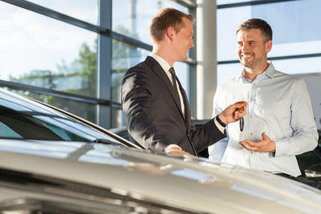 Photo of car dealer selling car to happy handsome buyer