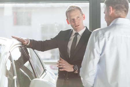 Photo of elegant salesman talking about new car model