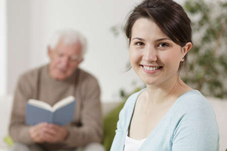 Old man reading a book and smiling young woman