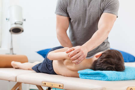 Close-up of physiotherapist using PNF stretching technique