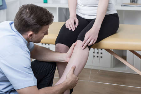 Young physiotherapist diagnosing patient with painful knee