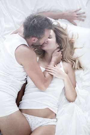 Image of couple during passionate foreplay in bed