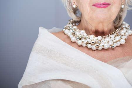 Rich, senior woman wearing elegant shawl and precious pearl jewellery