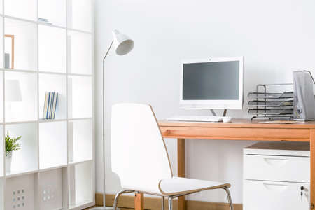 Light home office with simple wood desk, chair, computer and standing lamp