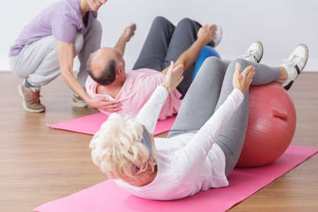 Senior exercising on gym ball with professional instructor.