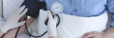 Close up of a nurse taking patient\'s blood pressure