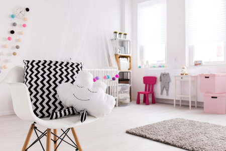 Close-up of white chair with pillows in cloud shape. In the background white cradle