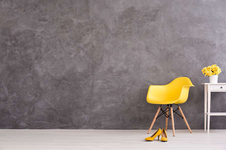 Yellow chair, shoes and flower on the table  on a background of a gray concrete wall
