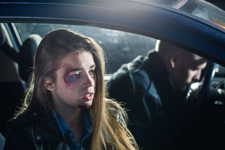 Hurt passenger sitting in the car with the unconscious driver