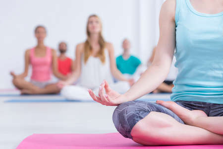 Closeup shot of a woman in sportswear sitting on a pink mat and doing yoga