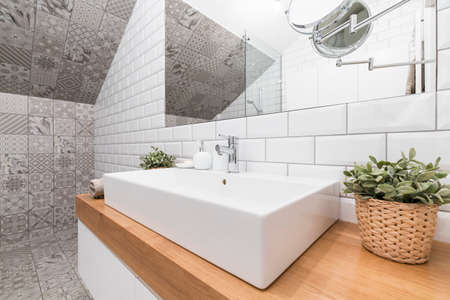 Contemporary bathroom corner with decorative tiles and a rectangular ceramic sink