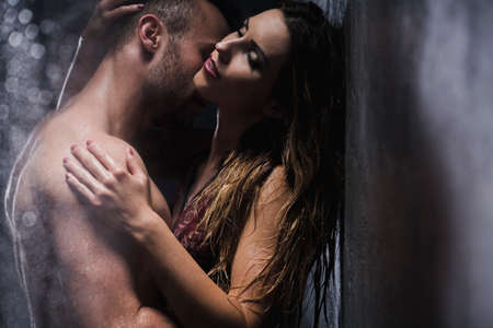 Sexy couple embracing and kissing under shower