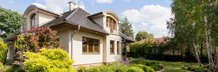 Panoramic shot of a modern house exterior with a beautiful garden