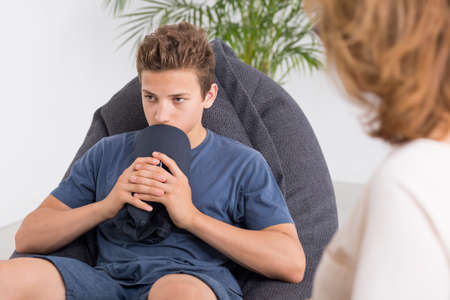 Depressed teenager talking with a mature psychologist, light interior