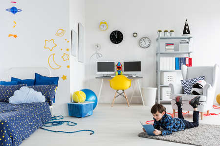 Shot of a fully furnished room for a young astronaut with cosmic themes on the wall and with a boy reading a book