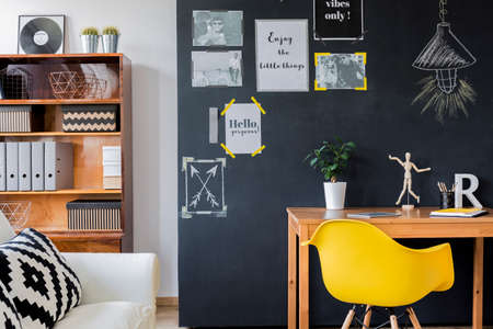 Modern designed room with a black wall with motivational posters on, with wooden desk, minimalistic yellow chair, rack with binders and white couch with cushions