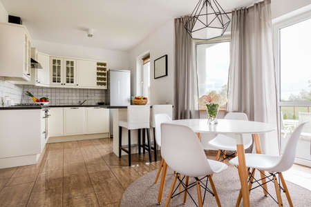 Light stylish interior with round table, white chairs and functional open kitchen