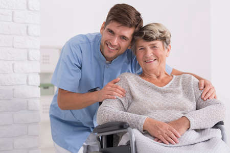 Male nurse hugging his senior woman patient sitting on a wheelchair
