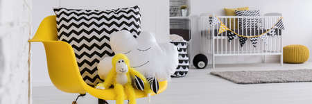 Close-up of yellow chair in baby\'s room with cute cloud shape pillow and monkey toy. In the background white cradle
