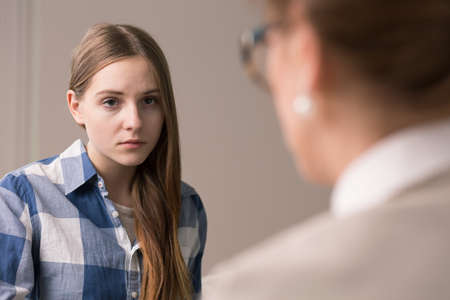 Sad and depressed teenager talking with psychologist