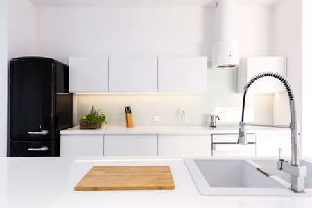 Photo for Cozy, white, lacquer kitchen in modern house with black retro fridge - Royalty Free Image