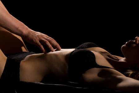Photo pour Man touching softly woman's body in black lingerie during sensual foreplay - image libre de droit