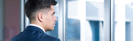 Profile of young businessman in suit looking through the window