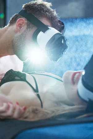 Man with googles looking at seductive woman lying on the bad only in her lingerie