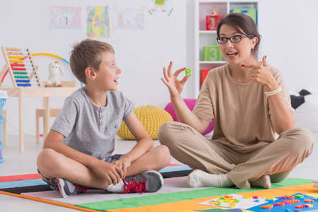 Young private tutor teaching child, sitting on floor together