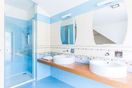 Blue bathroom with double sinks, mirrors and glazed shower