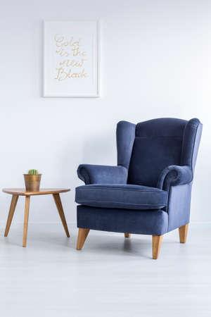 Foto de White room with blue upholstered armchair and side table - Imagen libre de derechos