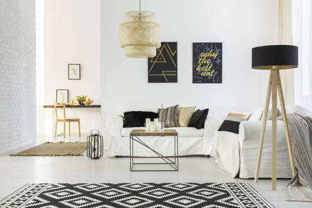 White home interior with sofa, table, lamp and carpet