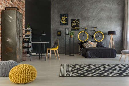 Grey apartment with bed, desk, chair, brick wall, yellow details