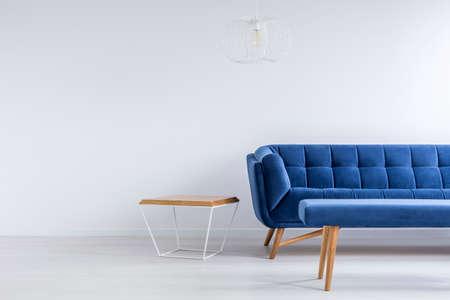 Foto de Room with blue sofa, bench, metal and wood table - Imagen libre de derechos